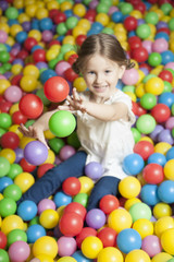 Young girl in ball pit throwing colored balls