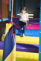 Young girl climbing down play gym
