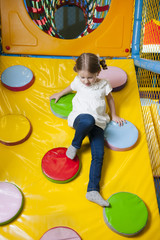 Young girl climbing down ramp in soft play centre