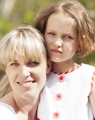 Close-up head shot of mother and daughter embracing