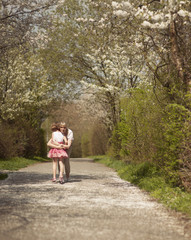 Mother hugging young girl in distance in a park