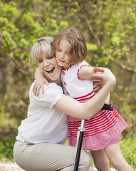 Mother and daughter hug in park with scooter