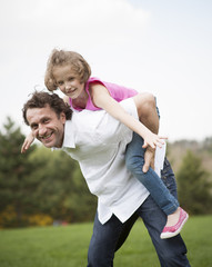 Father giving young daughter piggyback ride