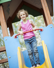 Young girl standing at top of slide in playground