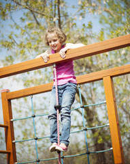 Young girl standing at top of rope and climbing frame
