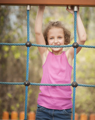 Half-length shot of young girl on climbing net
