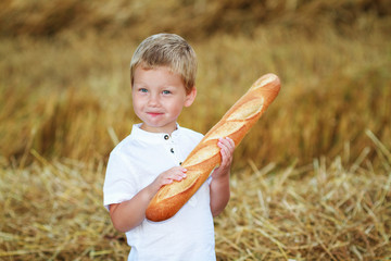 Child with long loaf in the wheat field