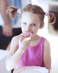 Young girl eating cake in kitchen