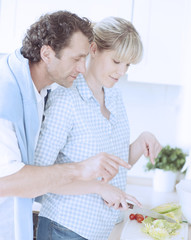 A couple making a healthy salad in the kitchen