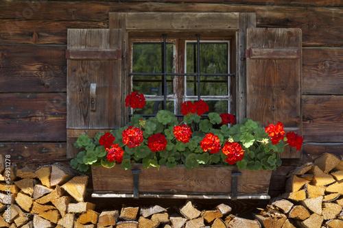 canvas print picture Fenster einer Almhütte mit Geranien und Holz