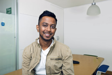 Young Indian man smiling at camera in his office