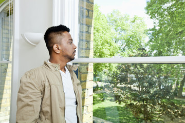 Young Indian man looking out window