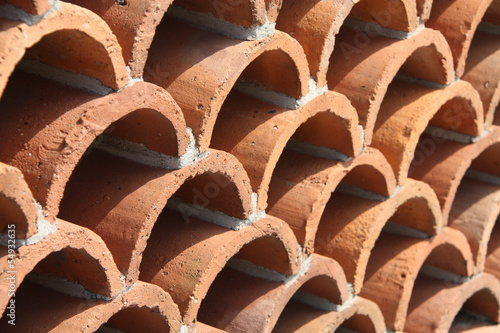 Abstract background of curved ceramic tiles or pots.