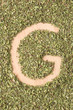 Letter G written with oregano