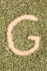 Letter G written with oregano