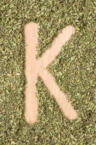 Letter K written with oregano