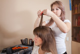 hairdresser working with long-haired girl