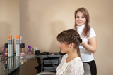 Female hairdresser works on woman hair