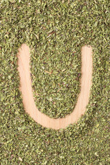 Letter U written with oregano