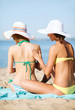girls applying sun cream on the beach