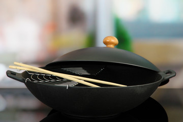 Black wok pan on kitchen oven, close up