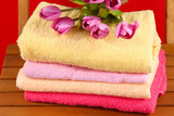 Towels and flowers on wooden chair on red background