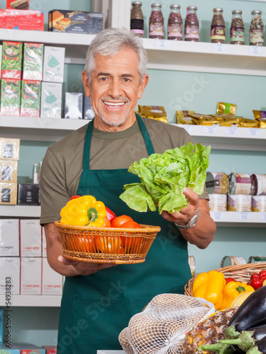Senior Salesman Selling Vegetables In Store