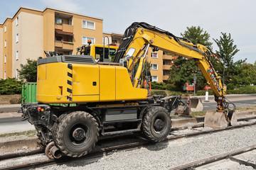 Ein gelber Bagger der auch auf Schienen fahren kann