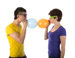 Man and woman with sunglasses blowing balloons