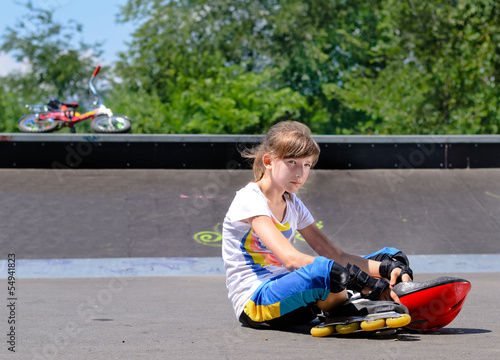 Girl with roller skates sitting lonely in the park