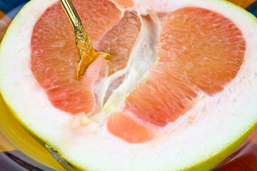 Gold spoon in pomelo fruit