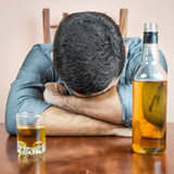 Drunk man sleeping with a whisky bottle on his table