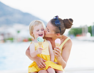 Mother kissing baby while eating ice cream