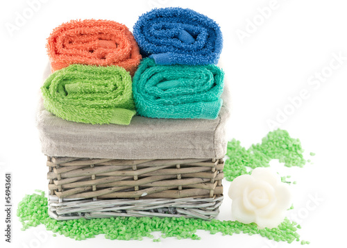 Colorful towels in a basket and soap isolated on white