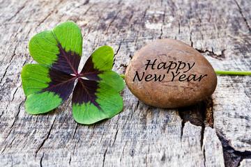 vierblättriges Kleeblatt mit Stein auf Holz, Happy New Year