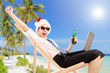 Excited man with santa hat on a beach chair holding a beer