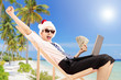Excited man with santa hat on a beach chair holding banknotes