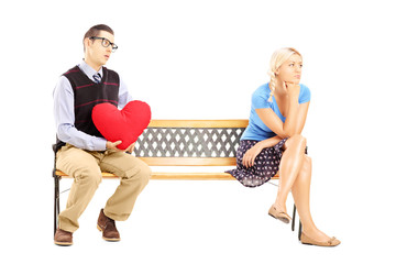 Male holding a red heart and disappointed female sitting
