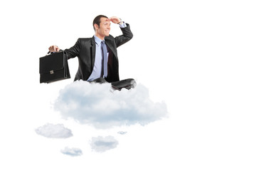 Young businessman with suitcase sitting on a cloud