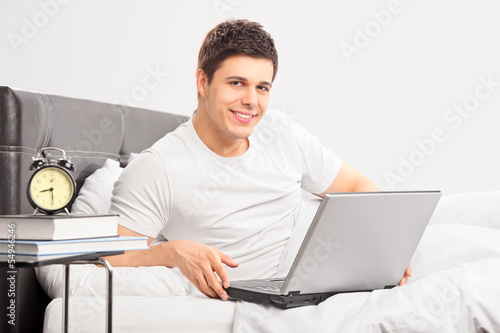 Smiling guy lying on a bed and working on a laptop
