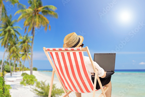 Young man on an outdoor chair working on a laptop, on a beach