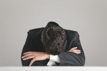 Portrait of a young businessman sleeping on desktop.