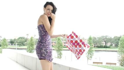 Pretty woman having fun while shopping on windy day