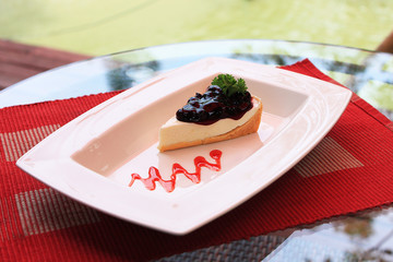 Blueberry cheesecake with strawberry sauce on white plate