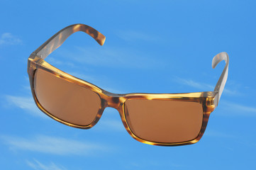 brown sunglasses on a bright blue sky