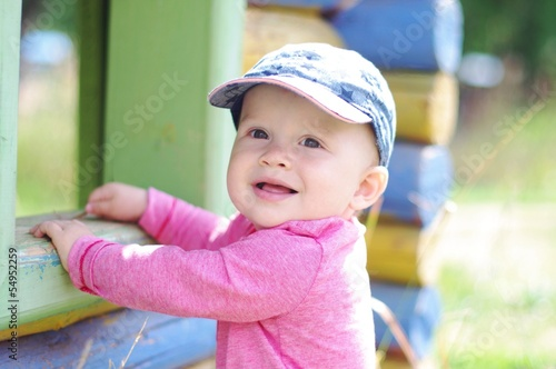 happy smiling baby age of 10 months on playground in summertime