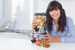 Happy brunette with juicer full of fruit