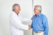 Arzt und Patient machen Handschlag