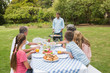 Cheerful extended family watching father at the barbecue
