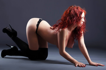 Image of red-haired topless model posing in studio